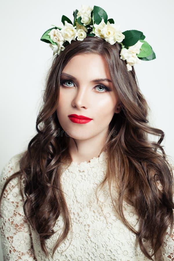 Menina bonita na coroa da flor Modelo da mulher com composição vermelha dos bordos do matiz foto de stock