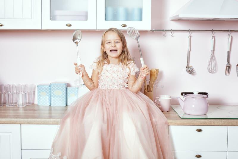 Menina bonita na cozinha e nos risos foto de stock