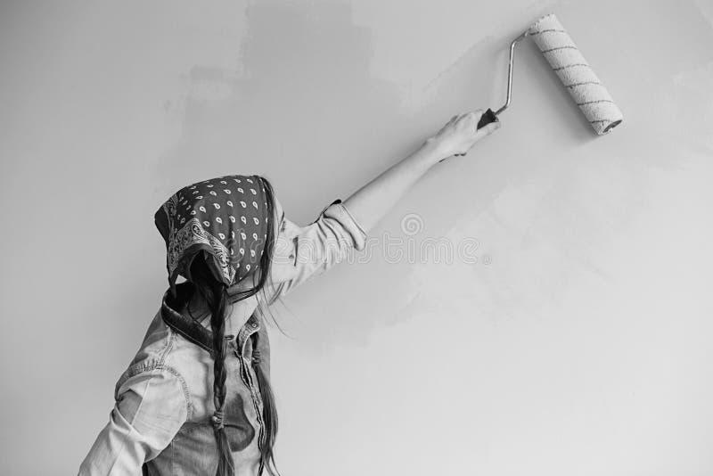 Menina bonita na faixa que pinta a parede com rolo de pintura imagem de stock royalty free