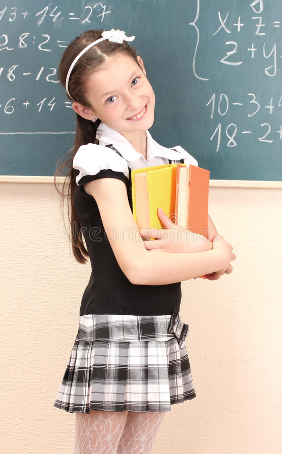 Menina bonita na farda da escola com livros imagem de stock royalty free