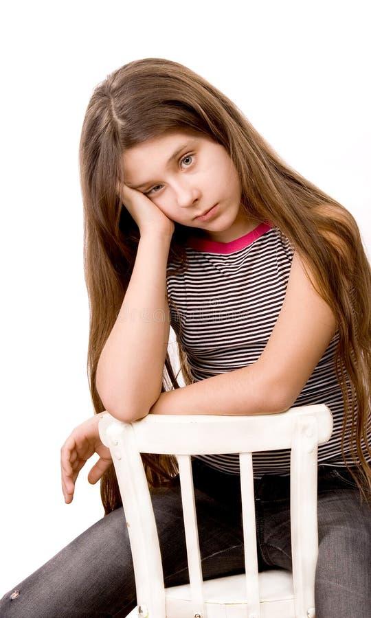 Menina bonita na idade de onze que sentam-se no branco fotografia de stock royalty free