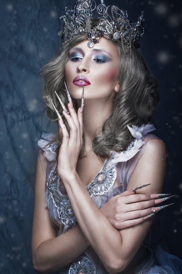 Menina bonita na imagem da rainha da neve, da composição criativa, do vestido transparente com coroa e da arte longa do prego imagem de stock