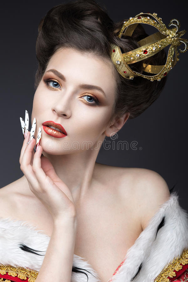 Menina bonita na imagem da rainha no envoltório com uma coroa na cabeça e nos pregos longos Face da beleza fotos de stock royalty free
