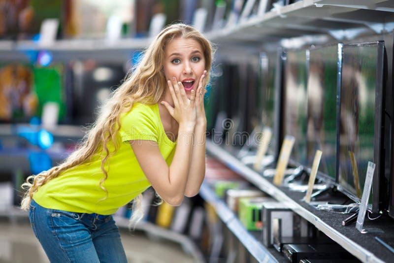Menina bonita na loja com tevês que quer saber preços fotos de stock royalty free