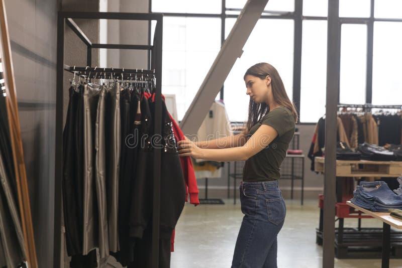 A menina bonita na loja está considerando uma camiseta vermelha imagem de stock