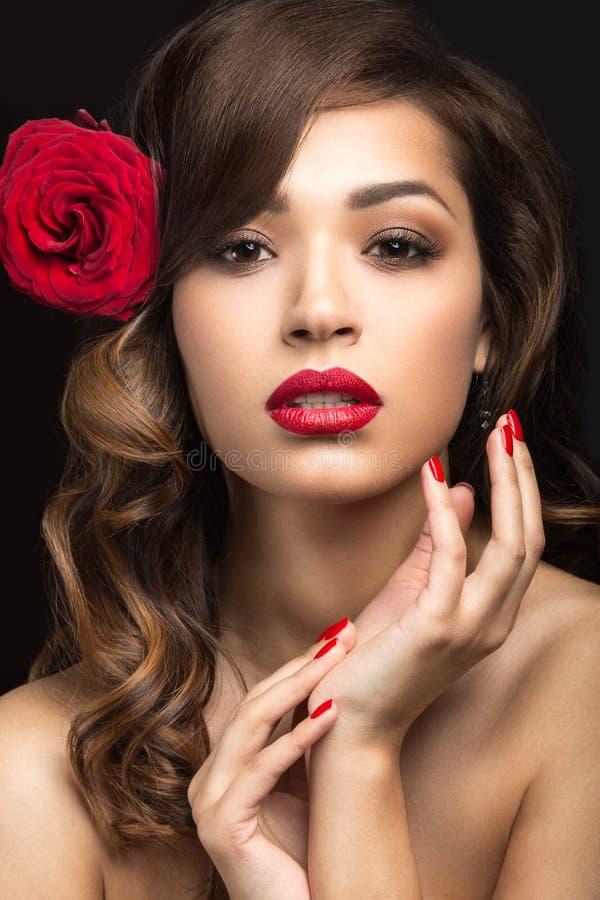 Menina bonita na maneira espanhola de Carmen com bordos vermelhos e uma rosa em seu cabelo imagens de stock royalty free