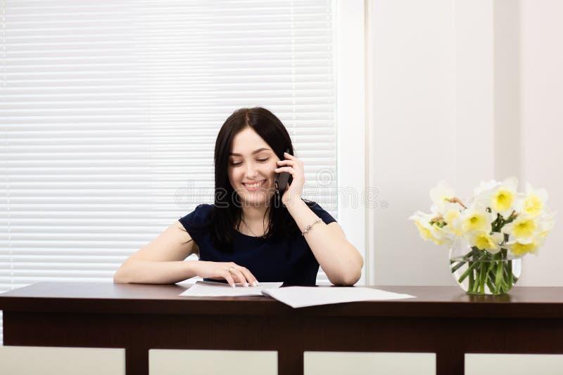 Menina bonita na mesa de recep??o que responde ? chamada no escrit?rio dental fotos de stock royalty free