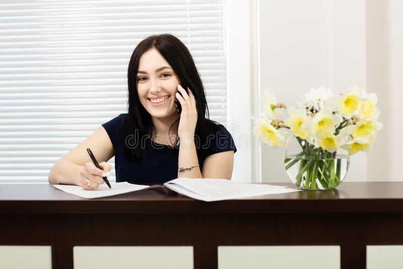 Menina bonita na mesa de recep??o que responde ? chamada no escrit?rio dental foto de stock
