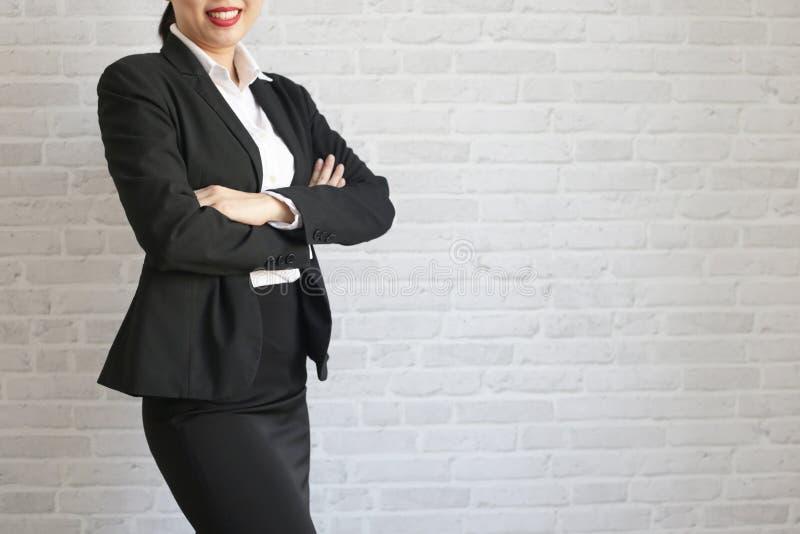 Menina bonita na posição preta do terno e sorriso em seu escritório Liga branca da divisória do corpo, vestida no pé da noiva imagem de stock