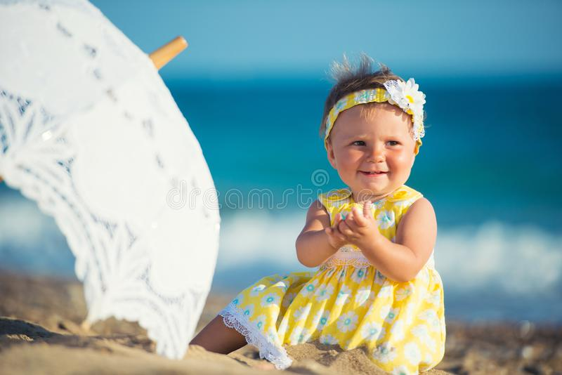 Menina bonita na praia com um guarda-chuva foto de stock