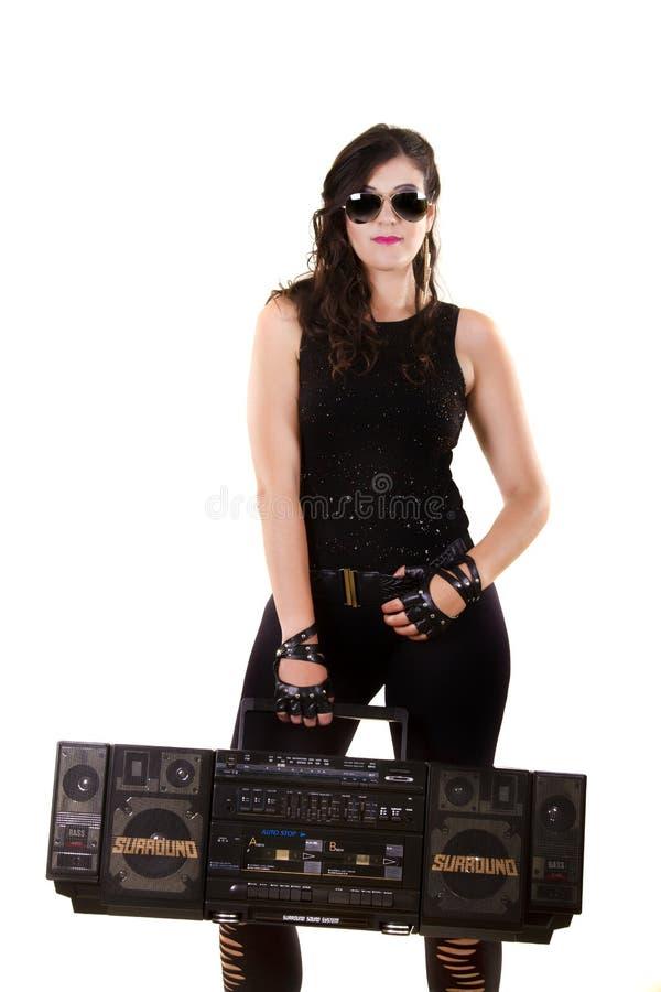 Menina bonita na roupa de couro escura que guarda um grande rádio retro imagem de stock royalty free