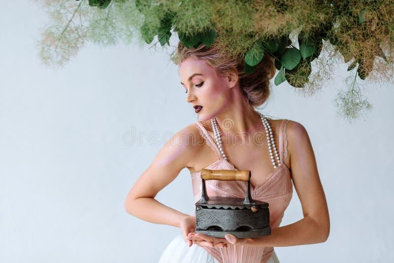 Menina bonita na roupa retro com ferro velho Estilo retro em um fundo branco foto de stock