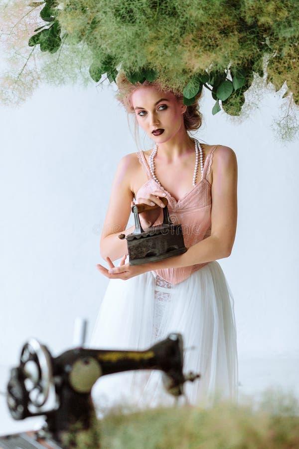 Menina bonita na roupa retro com ferro velho Estilo retro em um fundo branco fotos de stock royalty free