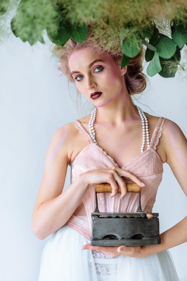 Menina bonita na roupa retro com ferro velho Estilo retro em um fundo branco foto de stock royalty free