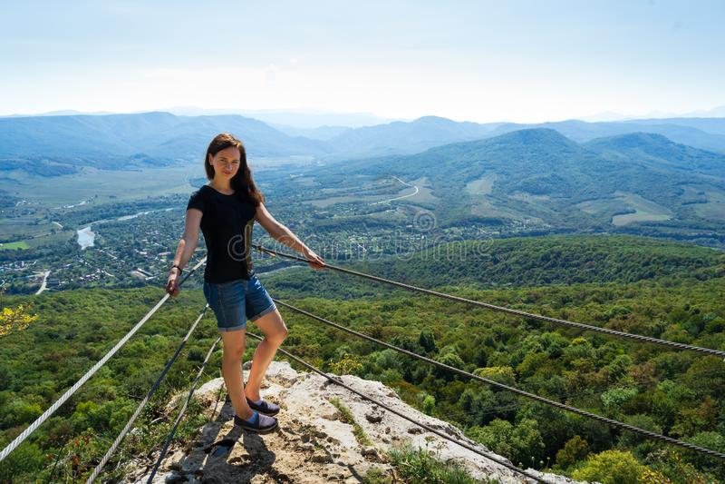 Menina bonita nas montanhas, na parte superior no short de um t-shirt preto e da sarja de Nimes imagens de stock
