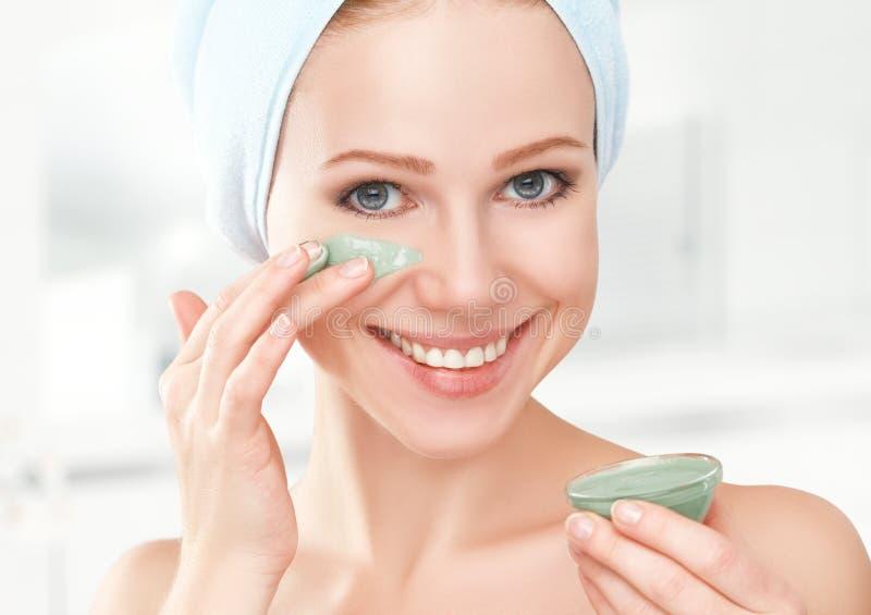 Menina bonita no banheiro e máscara para cuidados com a pele faciais imagens de stock