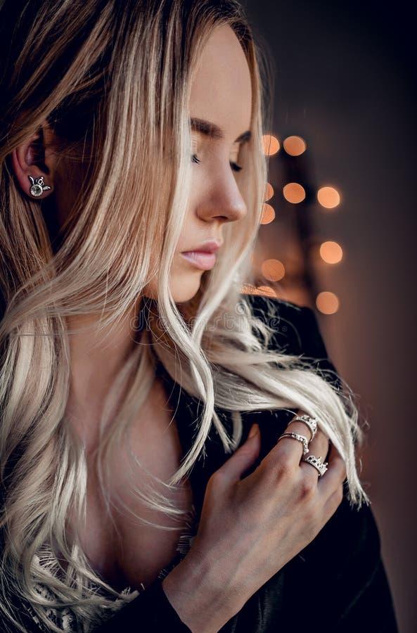 A menina bonita no bokeh dourado ilumina o fundo fotos de stock royalty free