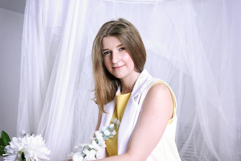 Menina bonita no branco, cortinas fotografia de stock