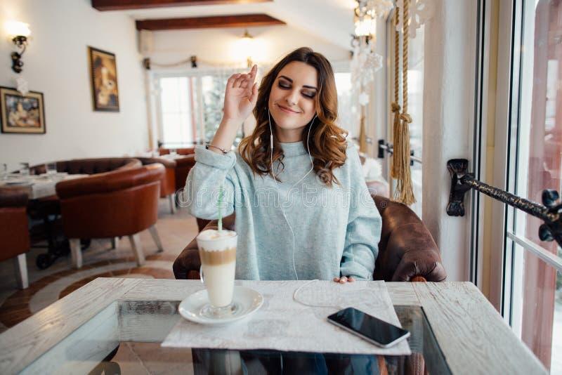 Menina bonita no café que escuta a música fotografia de stock royalty free