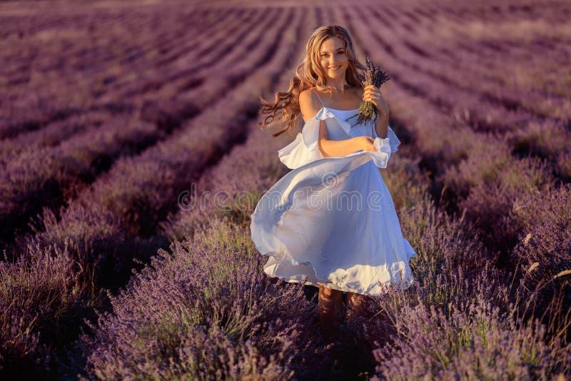 Menina bonita no campo da alfazema Mulher bonita no campo da alfazema no por do sol fotografia de stock
