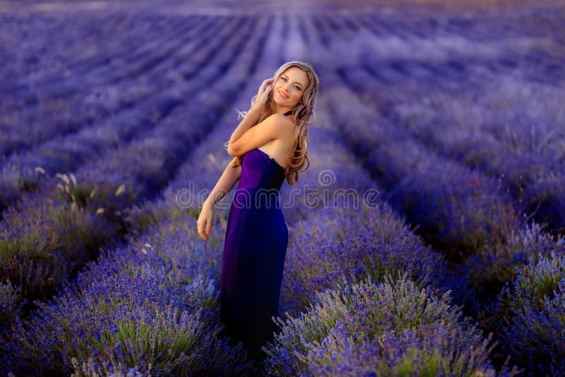 Menina bonita no campo da alfazema Mulher bonita no campo da alfazema no por do sol fotografia de stock royalty free