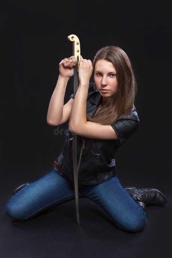 Menina bonita no casaco de cabedal com a espada no fundo preto fotos de stock