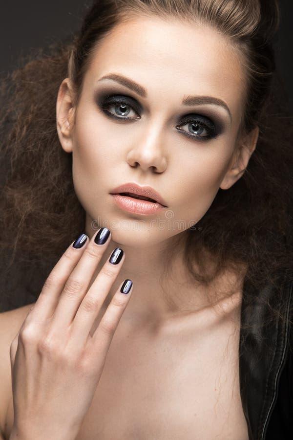 Menina bonita no casaco de cabedal com o olho de gato brilhante da composição e do tratamento de mãos Face da beleza Projeto do p imagens de stock