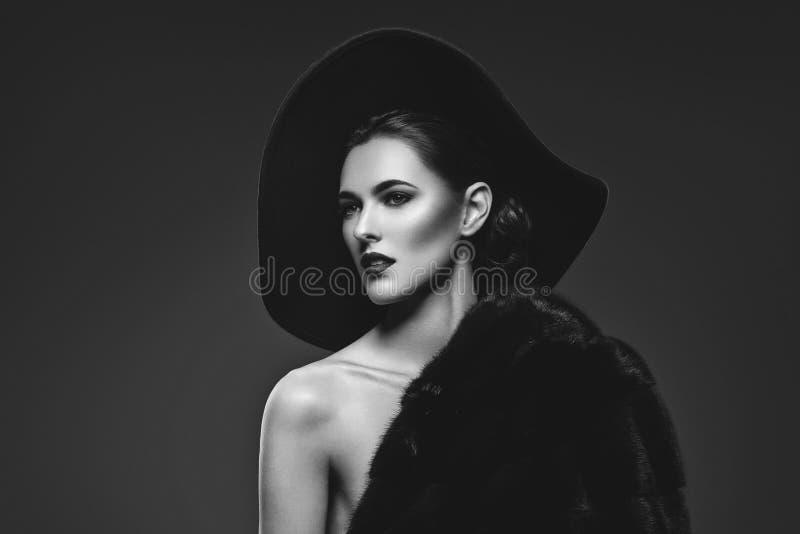 Menina bonita no casaco de pele e no chapéu imagens de stock royalty free