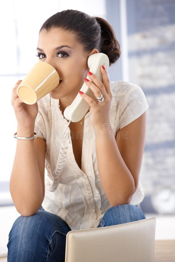 Menina bonita no chá bebendo do telefone fotos de stock royalty free