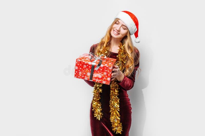 Menina bonita no chapéu de Santa Claus, em suas mãos um Christm fotografia de stock