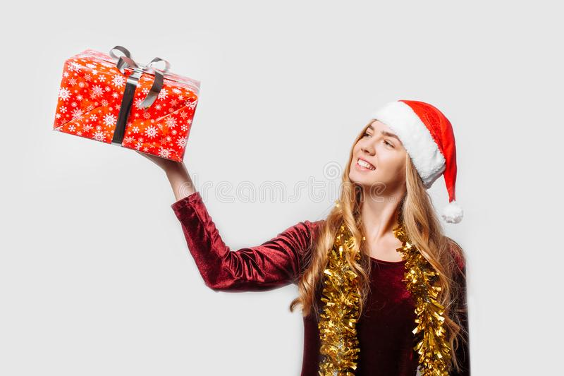 Menina bonita no chapéu de Santa Claus, em suas mãos um Christm imagem de stock royalty free
