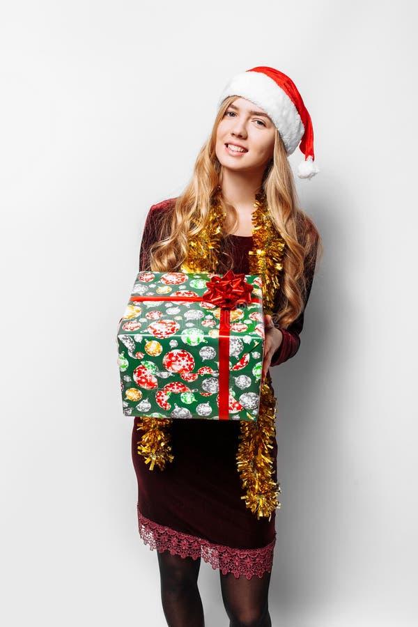 Menina bonita no chapéu de Santa Claus, em suas mãos um Christm fotos de stock