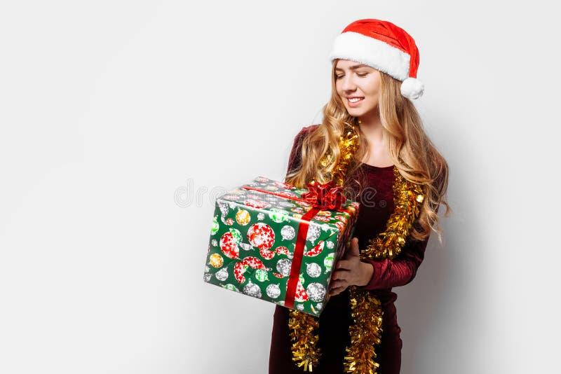 Menina bonita no chapéu de Santa Claus, em suas mãos um Christm imagem de stock