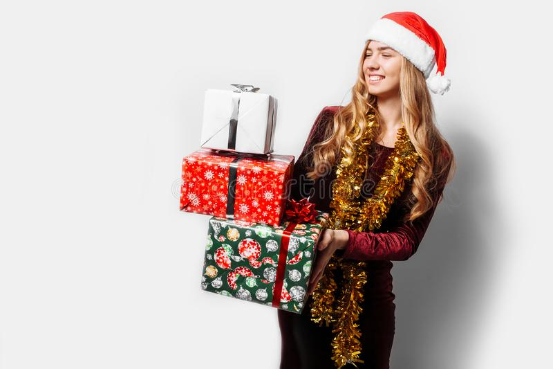Menina bonita no chapéu de Santa Claus, em suas mãos um Christm foto de stock