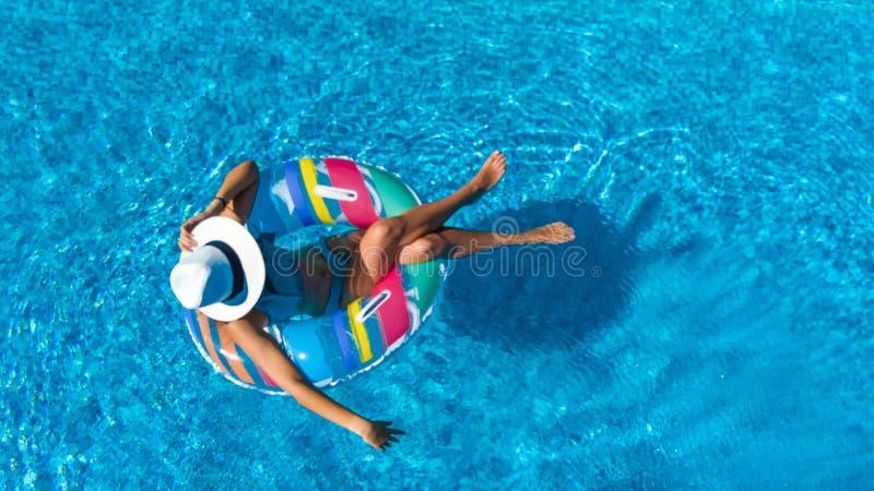 A menina bonita no chapéu na opinião superior aérea da piscina de cima de, mulher relaxa e nada na filhós inflável do anel e tem  imagens de stock royalty free