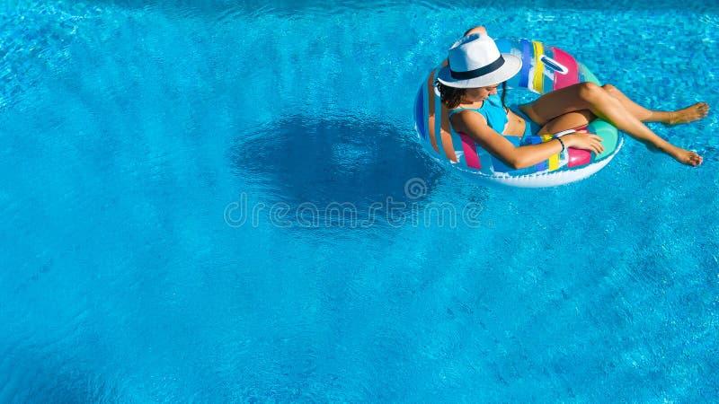 A menina bonita no chapéu na opinião superior aérea da piscina de cima de, mulher relaxa e nada na filhós inflável do anel e tem  fotos de stock royalty free