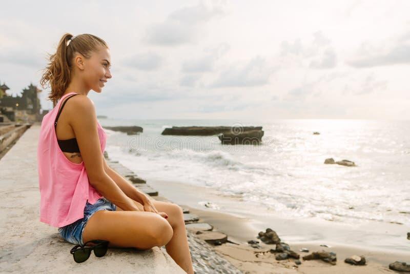 Menina bonita no equipamento desportivo na praia do oceano imagem de stock
