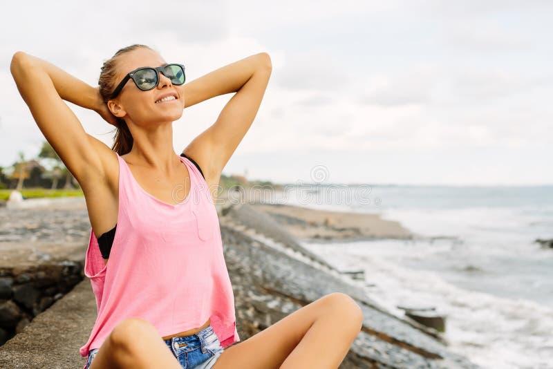 Menina bonita no equipamento desportivo na praia do oceano fotografia de stock