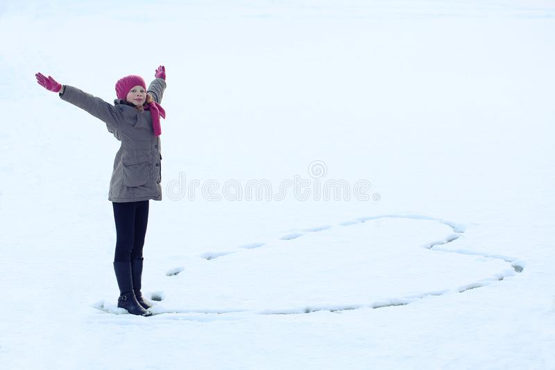 A menina bonita no inverno veste o coração de tiragem na neve Traço na neve fotos de stock royalty free