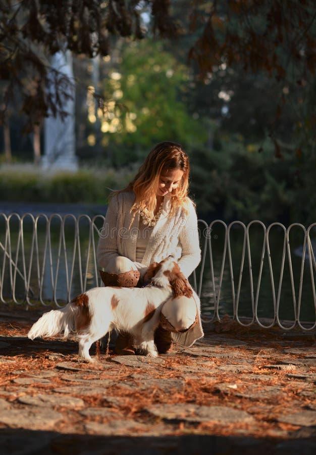 Menina bonita no parque que aprecia com seu rei descuidado Charles Spaniel do cão foto de stock