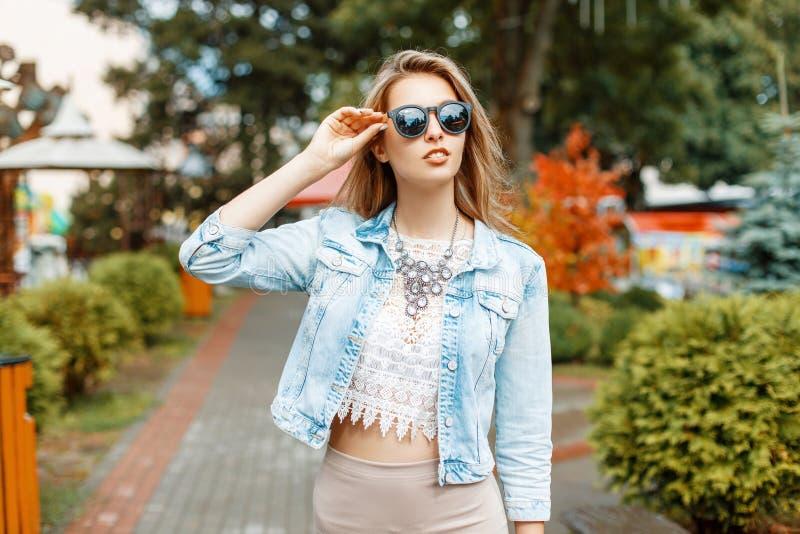 Menina bonita no passeio do revestimento dos óculos de sol e das calças de brim fotografia de stock