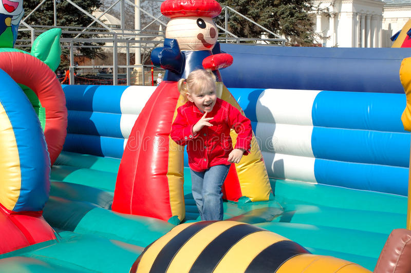 Menina bonita no passeio inflável. fotografia de stock