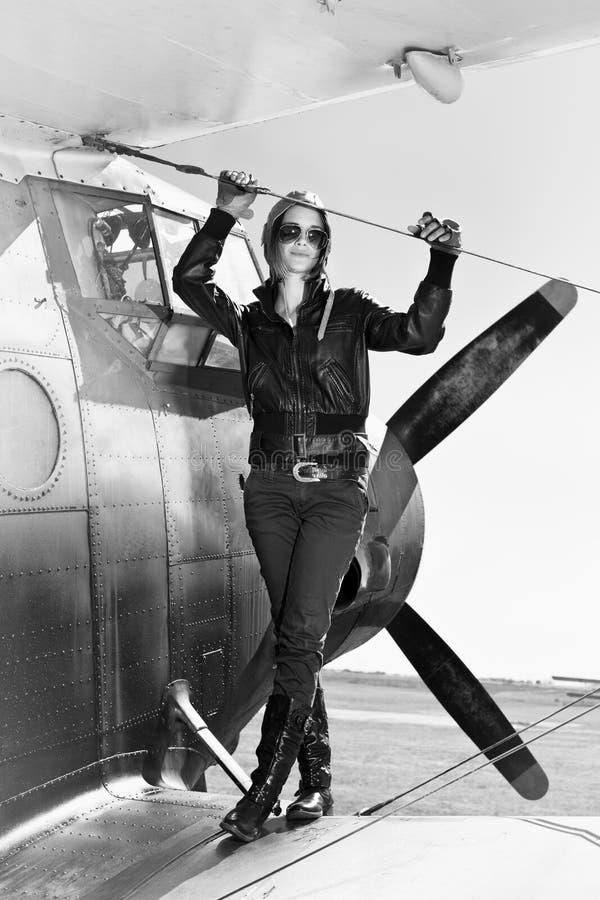 Menina bonita no revestimento preto que está em um avião da guerra. imagem de stock