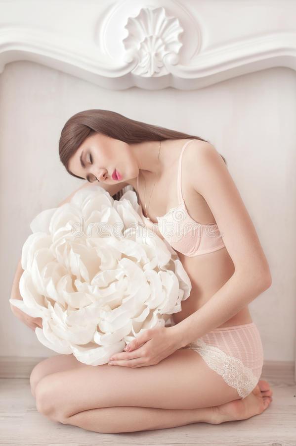 Menina bonita no roupa interior cor-de-rosa com a grande flor de papel fotos de stock royalty free