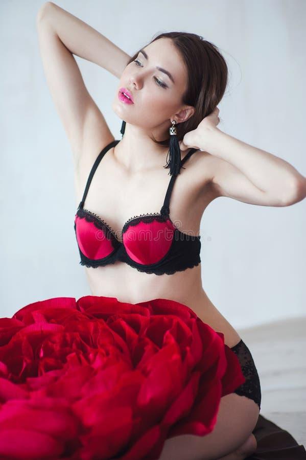 Menina bonita no roupa interior vermelho com a grande flor de papel fotografia de stock royalty free