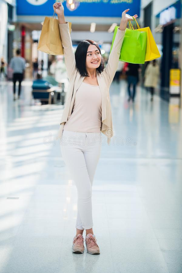 Menina bonita no shopping, olhando a câmera, sorrindo extensamente e guardando sacos de compras coloridos nas mãos levantadas fotos de stock royalty free
