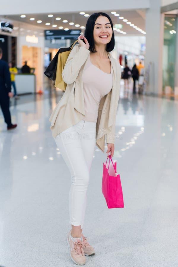 Menina bonita no shopping, olhando a câmera, sorrindo extensamente e guardando sacos de compras coloridos nas mãos levantadas imagem de stock