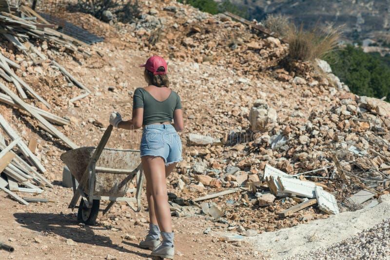 Menina bonita no short, t-shirt e no tampão repicado vermelho que empurra um carrinho de mão com cimento foto de stock