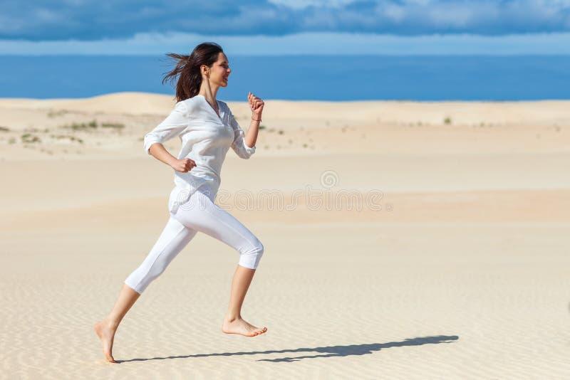 Menina bonita no sportswear que corre no deserto fotografia de stock