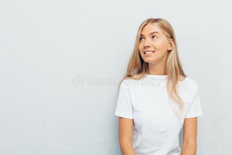 Menina bonita no t-shirt branco, com expressão pensativa e sonhadora em sua cara, com fundo cinzento da parede fotografia de stock